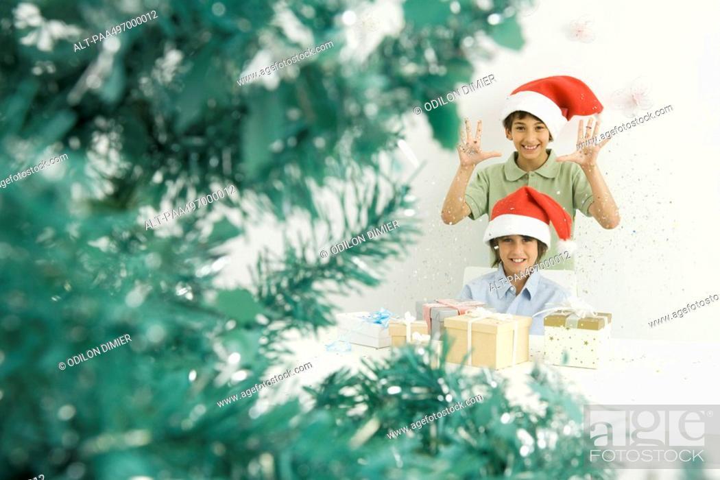 Stock Photo: Boys with Christmas gifts, wearing Santa hats, smiling at camera.