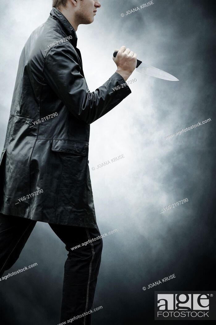 Stock Photo: a man in dark clothes with a knife.