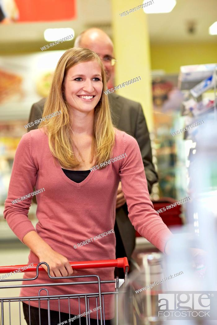 Stock Photo: Germany, Cologne, Man and woman waiting in supermarket, smiling.