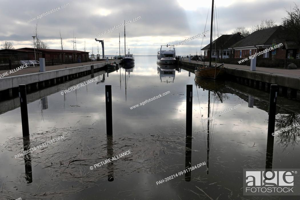 Stock Photo: 14 February 2020, Mecklenburg-Western Pomerania, Wustrow: In the water of the Bodden harbour the dark clouds are reflected.