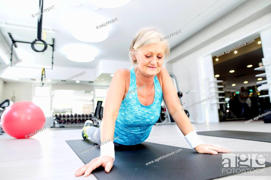 Stock Photo: Mature woman doing gymnastics in fitness gym.