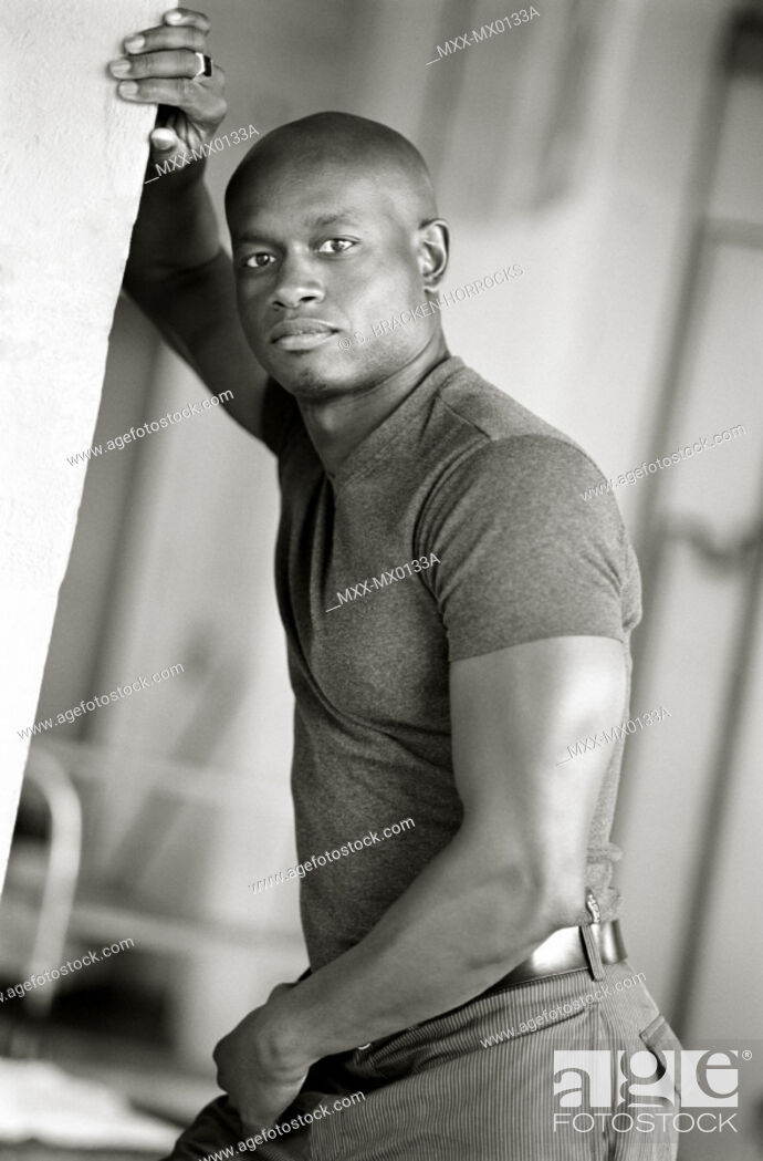 Stock Photo: Portrait of African-american man leaning against wall.