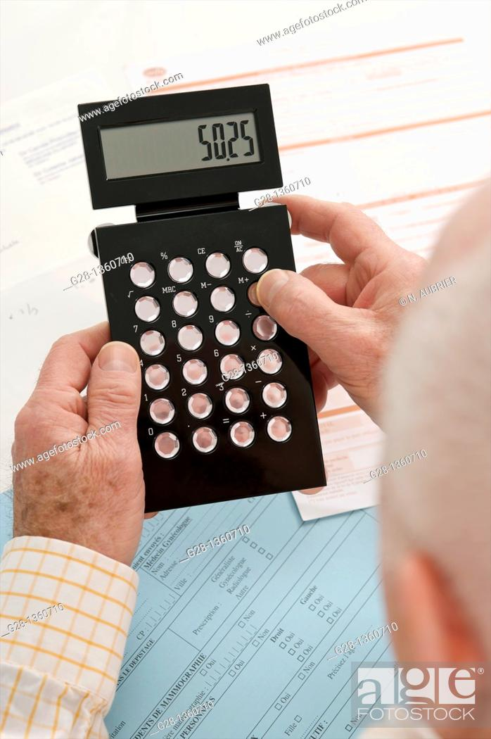 Senior Man calculating with a calculator in hand with