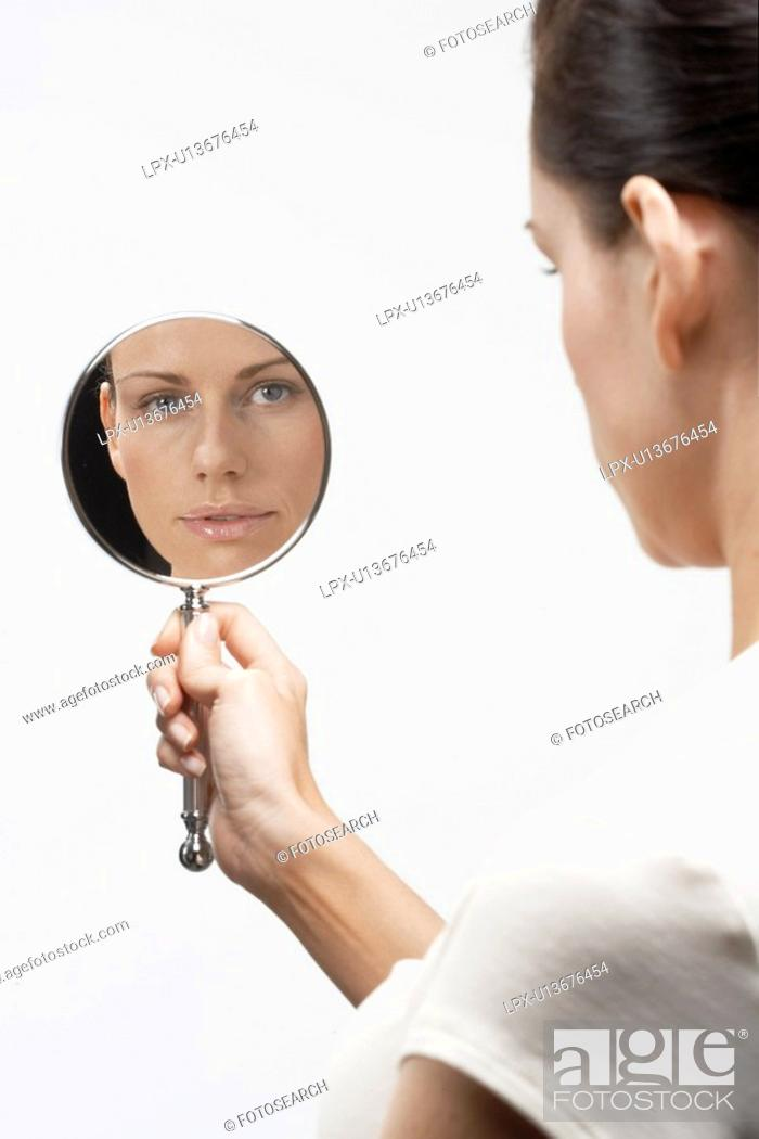 Stock Photo: Woman holding hand mirror.