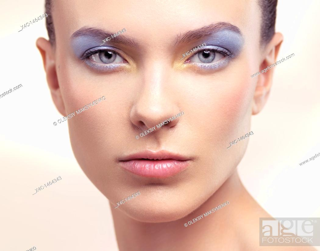 Stock Photo: Closeup beauty portrait of a young woman face with soft pastel blue color makeup.