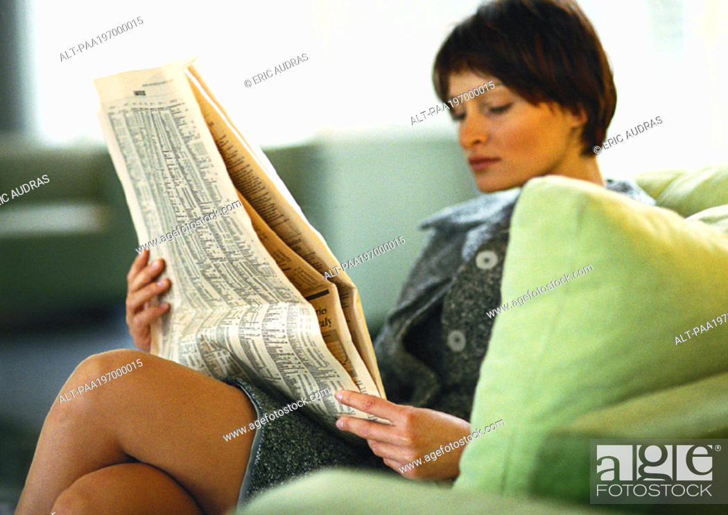 Stock Photo: Businesswoman sitting with legs crossed, reading paper.