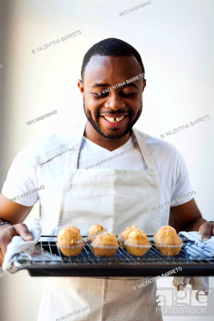 Stock Photo: Happy young man holding tray with muffins.