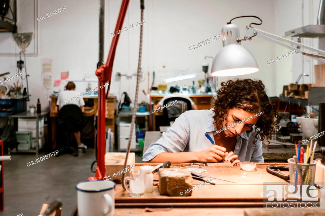 Stock Photo: Female jeweller drawing at workbench.