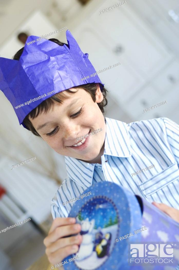 Stock Photo: Christmas day, portrait of a little boy opening his present in a blue box, indoors.