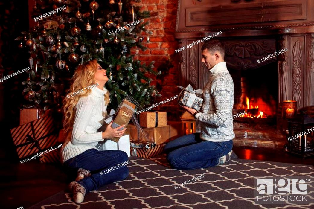Stock Photo: Man and woman in knitted sweater sitting on the floor by the fireplace.