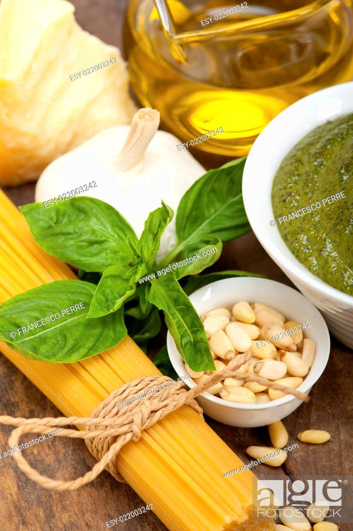 Stock Photo: Italian traditional basil pesto pasta ingredients parmesan cheese pine nuts extra virgin olive oil garlic on a rustic table.