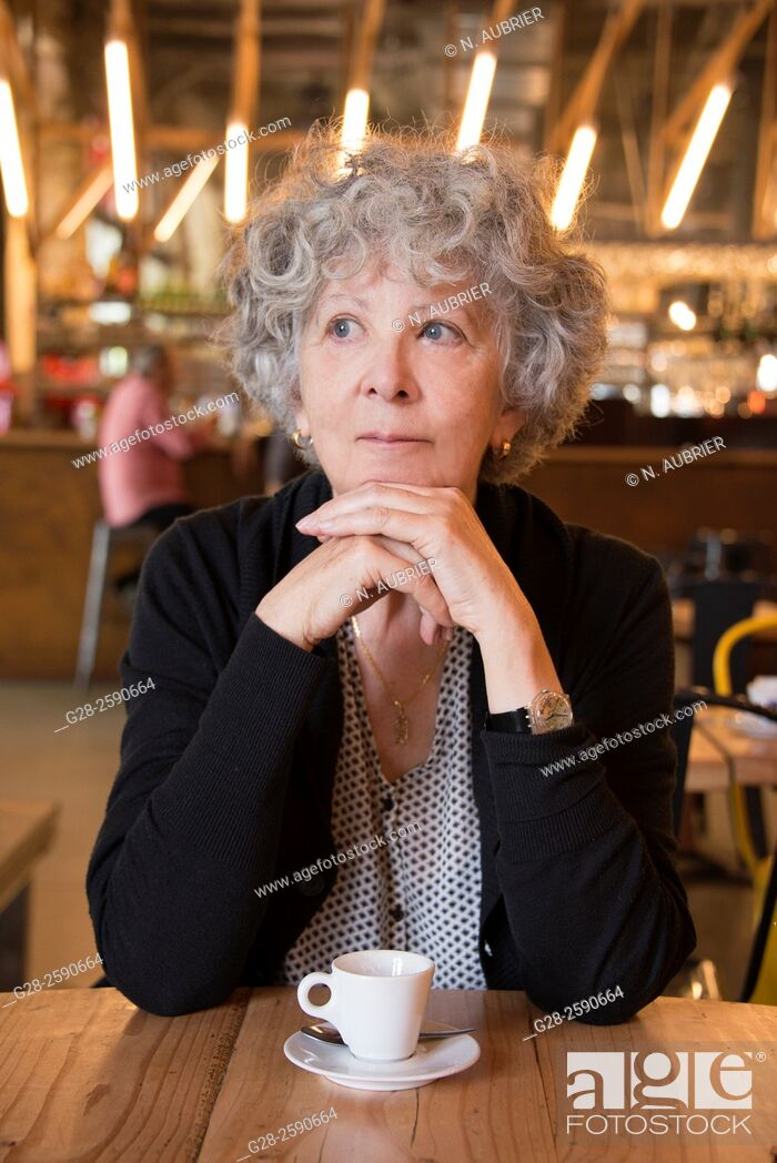 Stock Photo: Beautiful senior woman, with grey hair, happy looking, thoughtful, with head resting on her clasped hands, elbows on table, in a cafe.