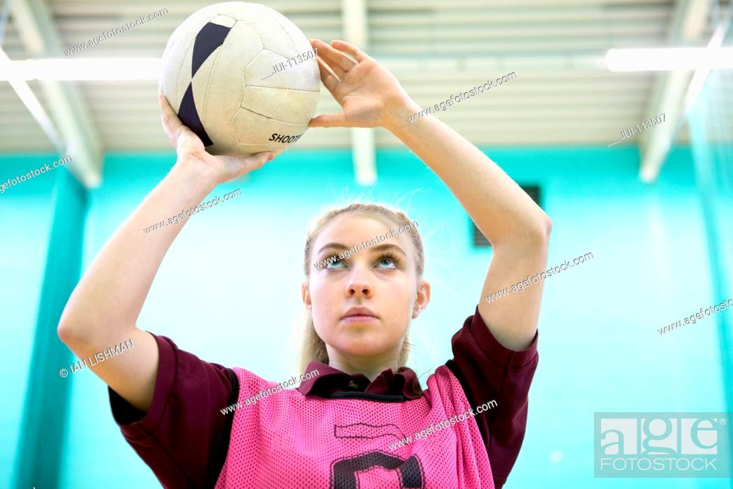 Stock Photo: Focused high school student playing netball in gym class.