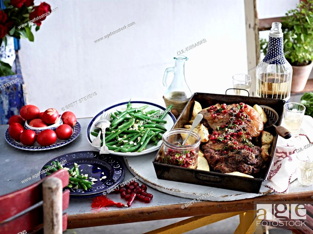 Stock Photo: Still life of roasted lamb with pomegranate seeds and vegetables.