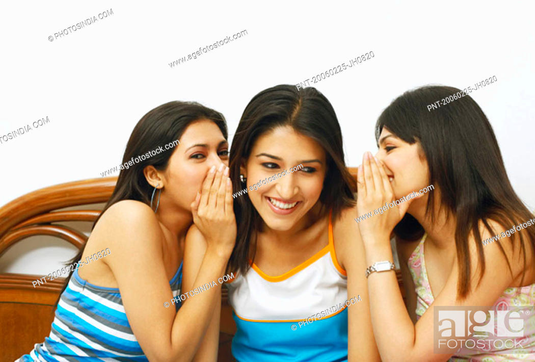 Stock Photo: Close-up of two young women whispering into their friends ears.