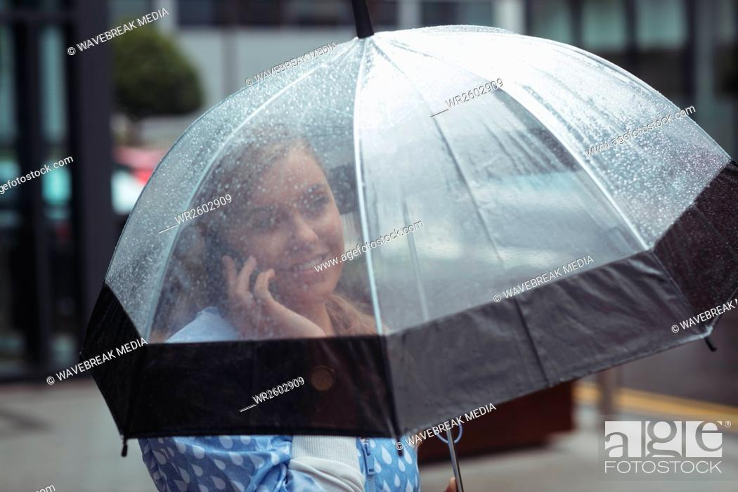 Stock Photo: Woman holding umbrella while talking on mobile phone.
