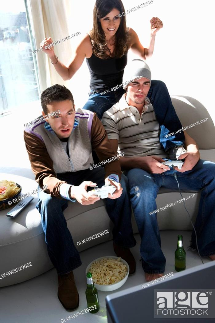 Stock Photo: Two young men and a young woman playing video game.