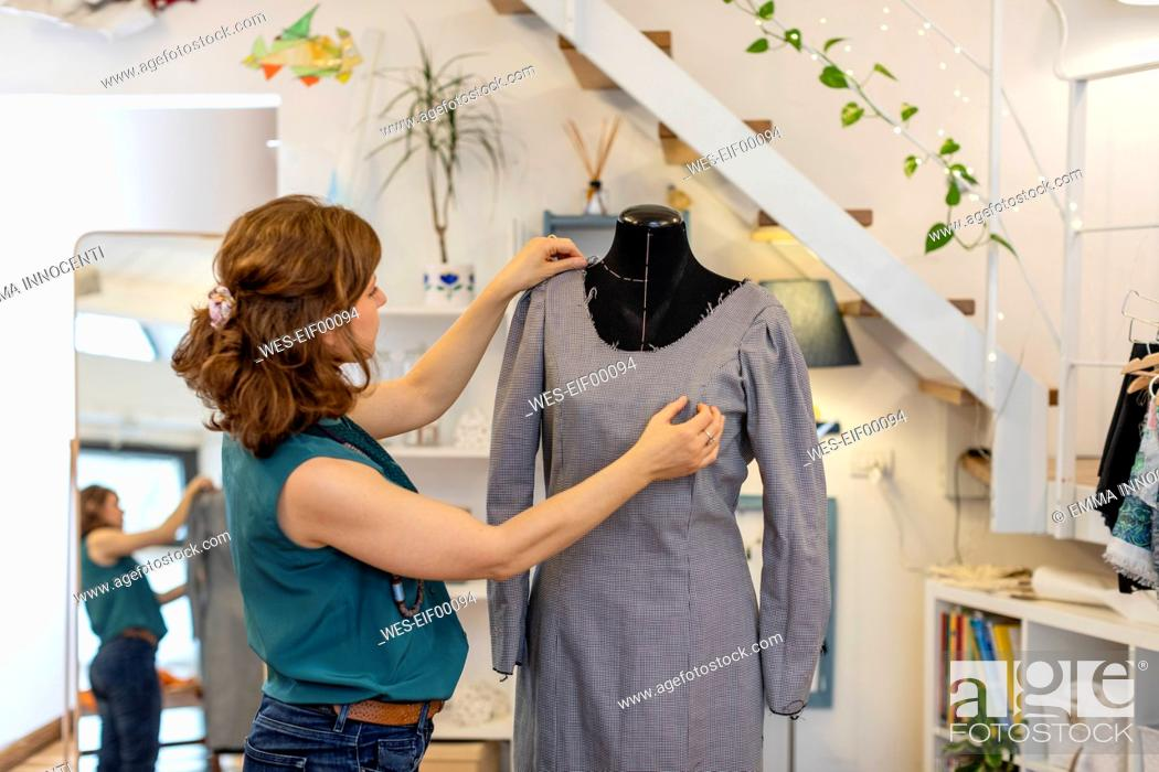 Stock Photo: Female design professional dressing mannequin with gray dress at atelier.