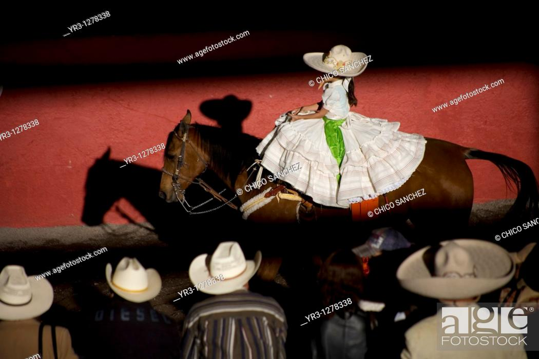 Stock Photo: Spectators watch a Mexican amazona ride her horse at the National Charro Championship in Pachuca, Hidalgo State, Mexico. Escaramuzas are similar to US rodeos.