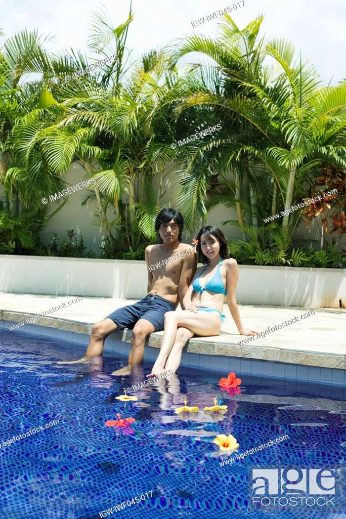 Stock Photo: A young couple sitting near pool.