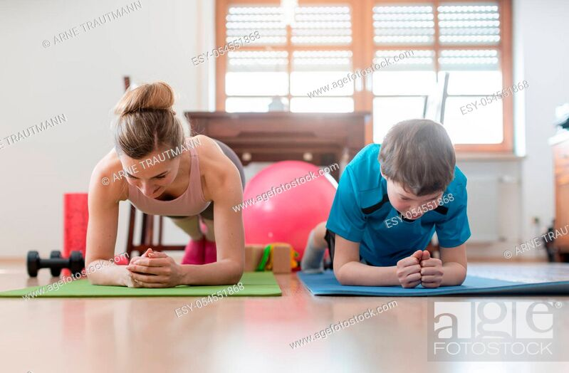 Stock Photo: Family in self quarantine during Covid-19 crisis staying fit at home exercising in the living room.