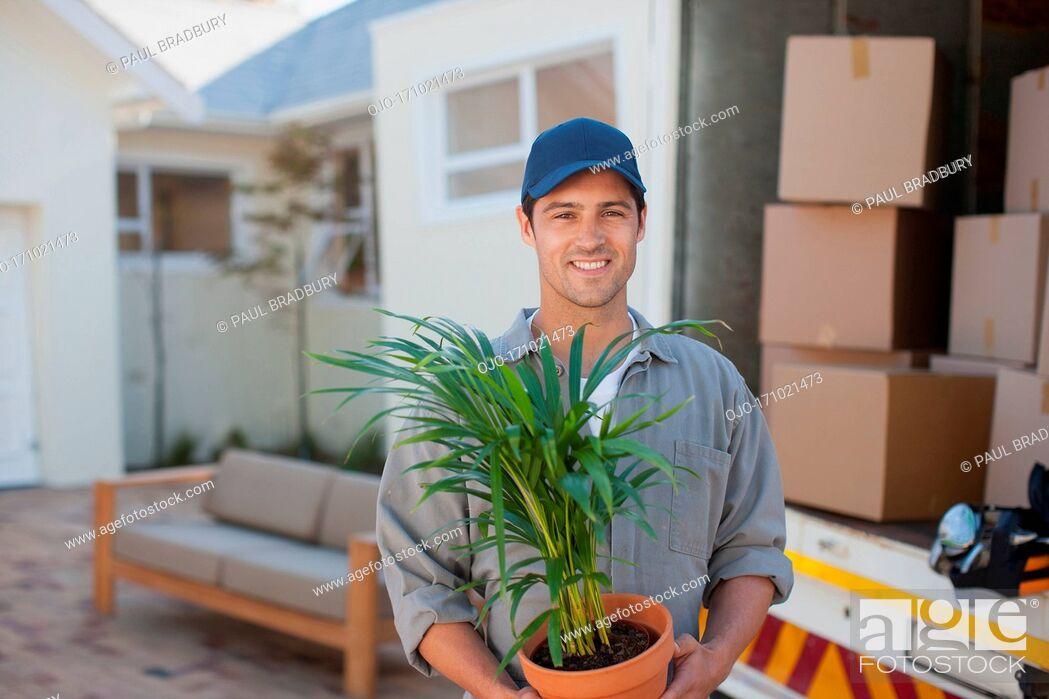 Stock Photo: Smiling man carrying Flowerpot moving van.