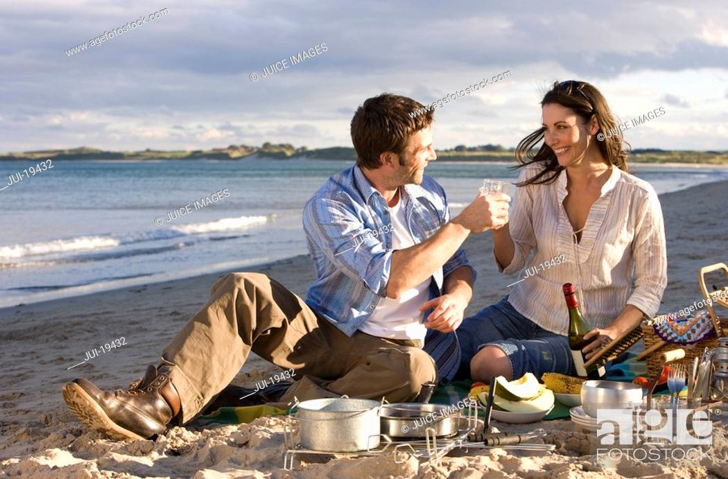 Stock Photo: Couple toasting champagne on beach.