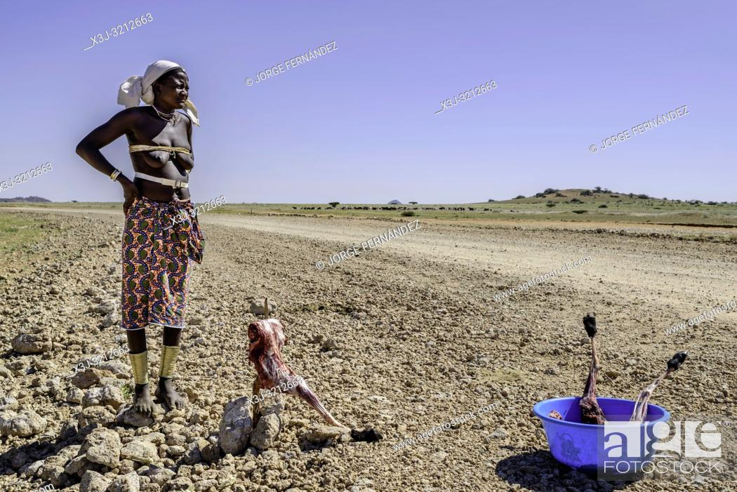Stock Photo: Barefoot Mucubale woman standing on the rocks near by the road trying to sell pieces of meat to the few drivers that travel on the very remote Angolan desert.