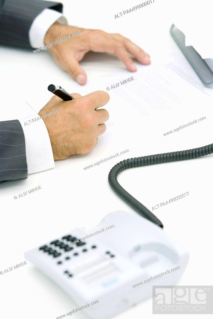 Stock Photo: Man signing document, cropped view, landline phone off the hook in foreground.