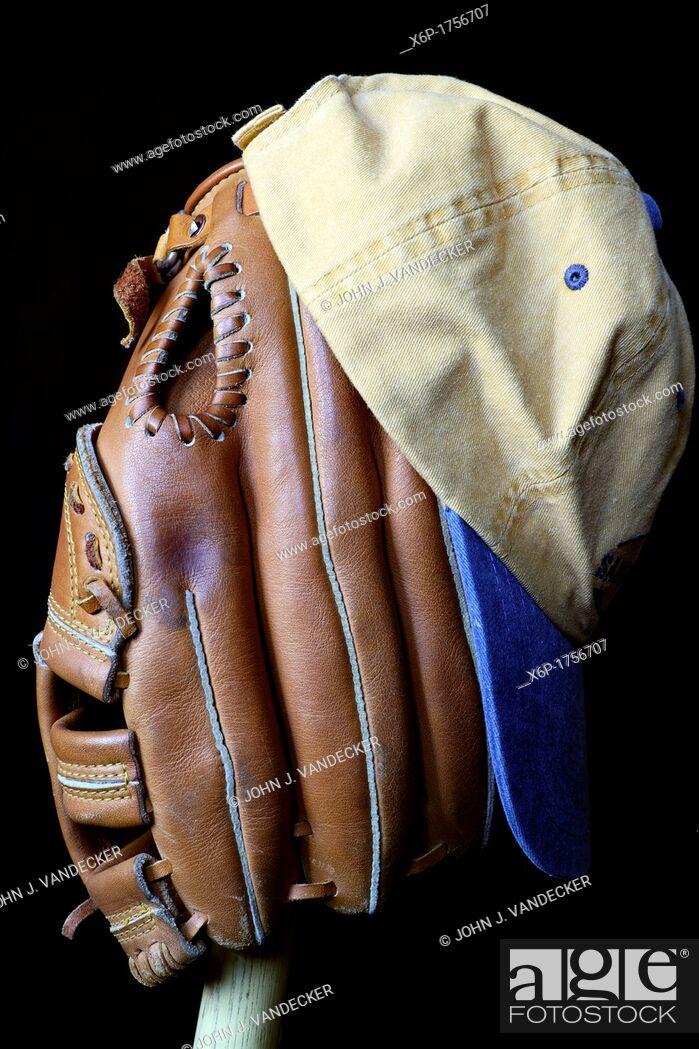 Photo de stock: Wait till next year  A baseball glove and cap sitting on a wooden bat.