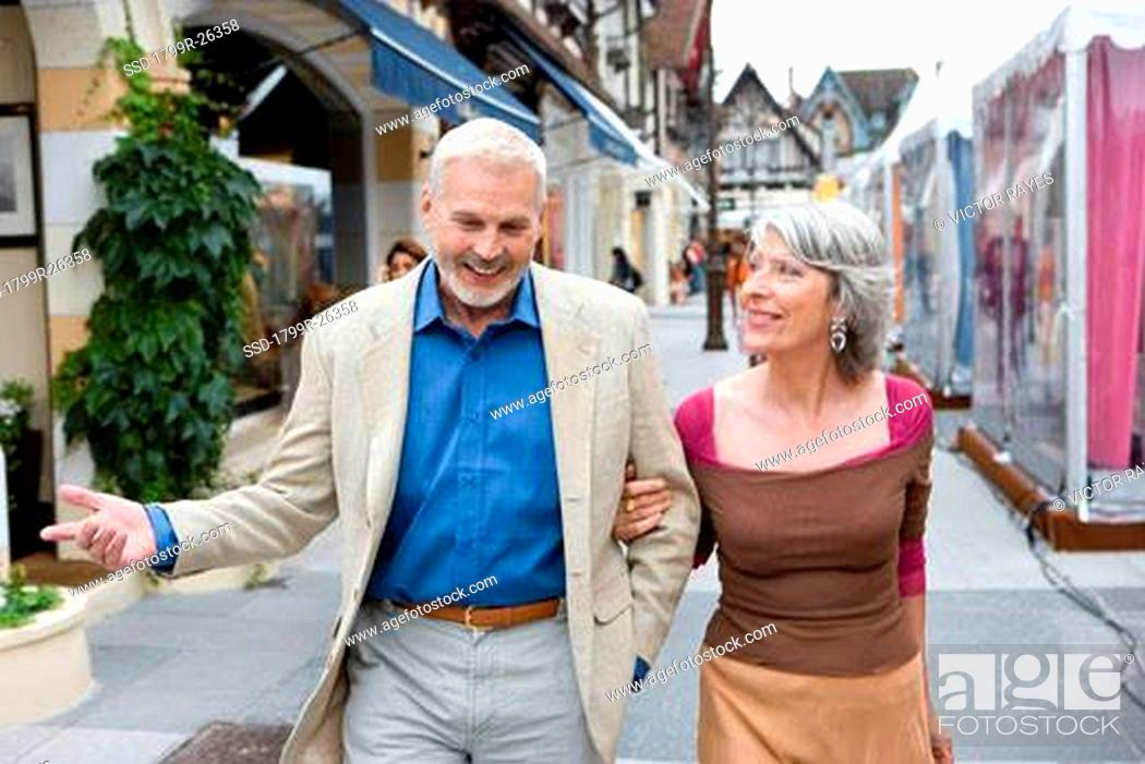 Stock Photo: Mature couple walking in a shopping district.