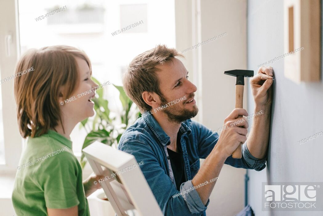 Stock Photo: Son watching father driving a nail into the wall at home.