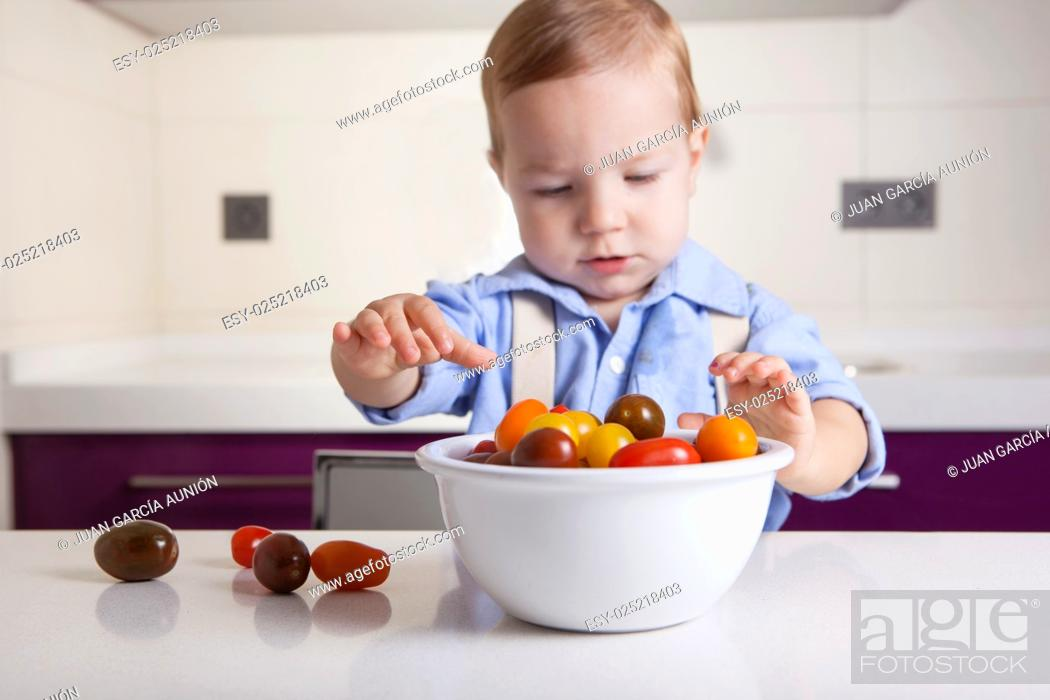 Stock Photo: Baby boy playing with ripe colorful cherry tomatoes. Education on healthy nutrition for children concept.