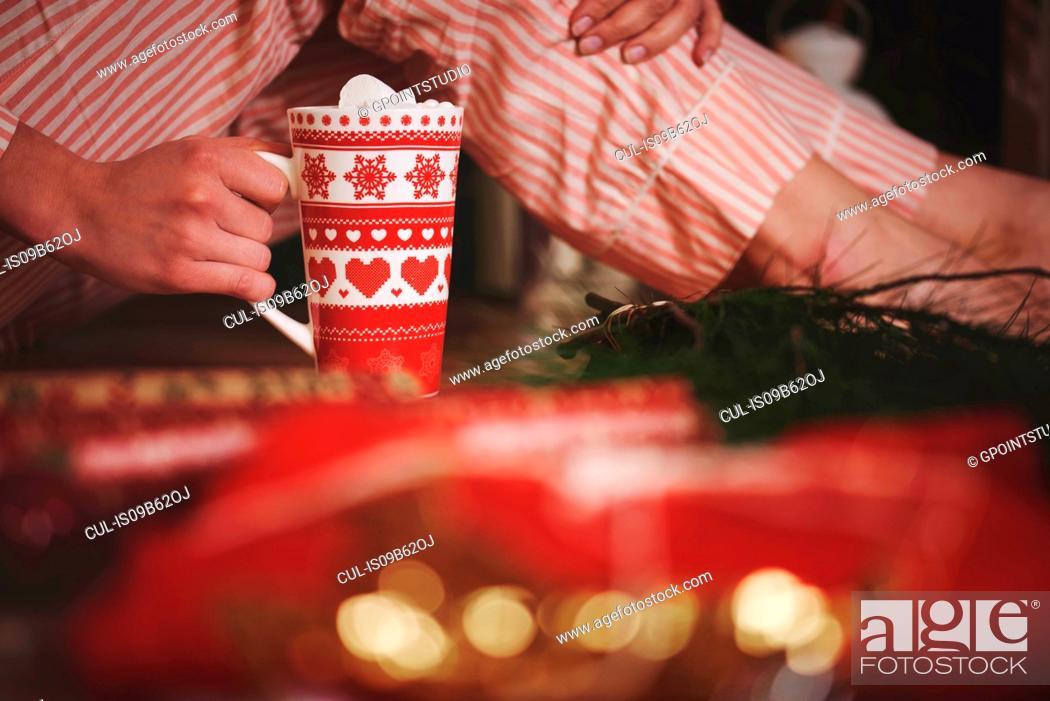 Stock Photo: Woman holding hot chocolate in festive mug.