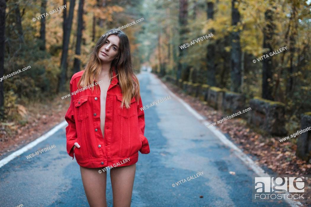 Stock Photo: Portrait of young woman standing on country road wearing red jacket.