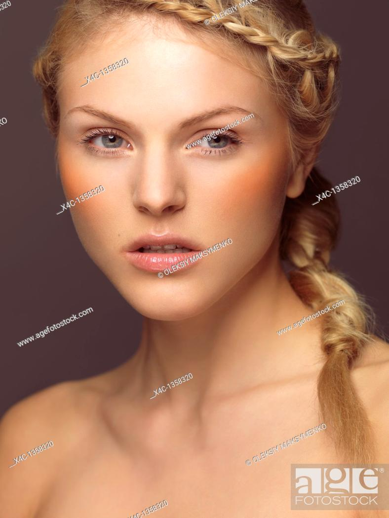 Stock Photo: Beauty portrait of a young woman with a braid and orange blush.