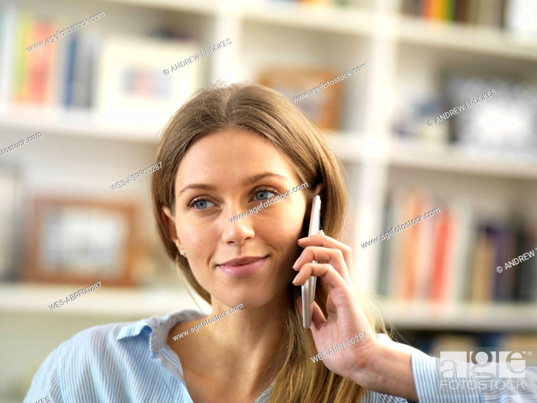 Stock Photo: Young woman on cell phone at home.
