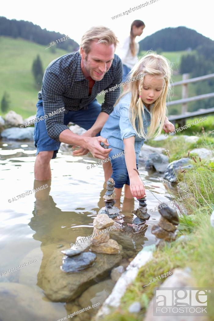 Stock Photo: Father And Daughter Playing With Stones In Stream.