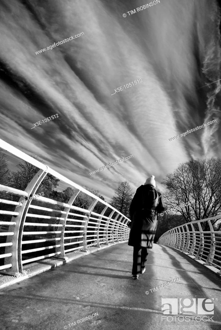 Stock Photo: Rearview woman walking over bridge, monochrome.