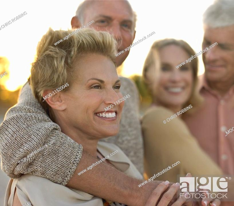 Stock Photo: Senior couples relaxing together on beach.