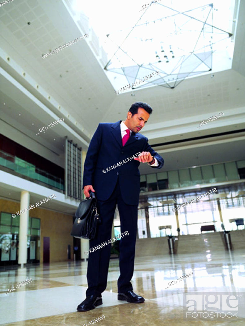 Stock Photo: Arab businessman looking at his wristwatch.