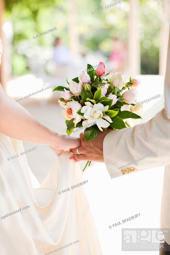 Stock Photo: Close up of bride and groom holding bouquet.
