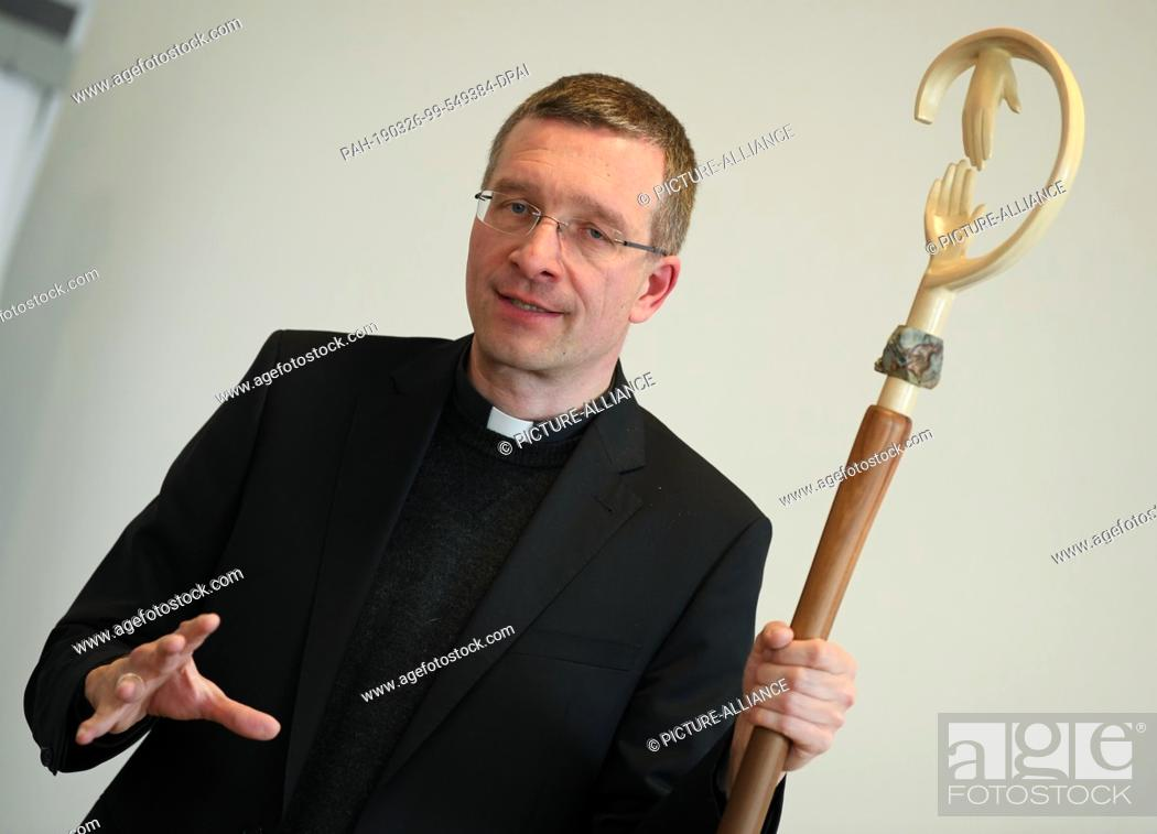 Stock Photo: 26 March 2019, Hessen, Fulda: The future bishop of Fulda Michael Gerber presents during a press conference in the seminary his bishop's staff made of chestnut.