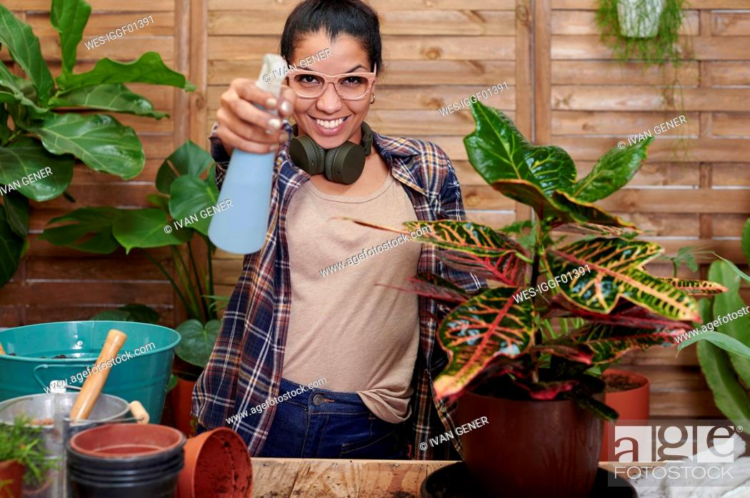 Stock Photo: Portrait of a smiling young woman gardening on her terrace.