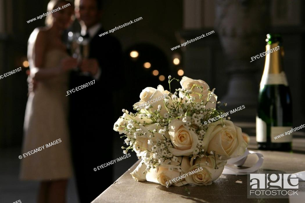 Stock Photo: Bouquet of roses with a couple in the background.