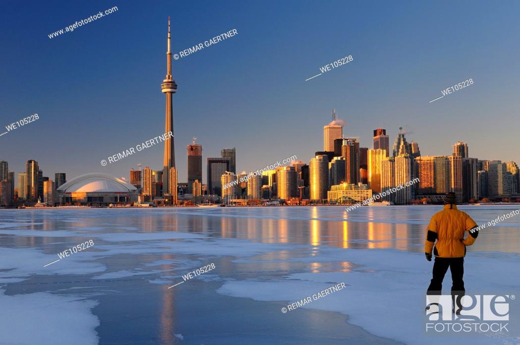 Stock Photo: Man standing on frozen Lake Ontario ice looking at Toronto city skyline at sunset.