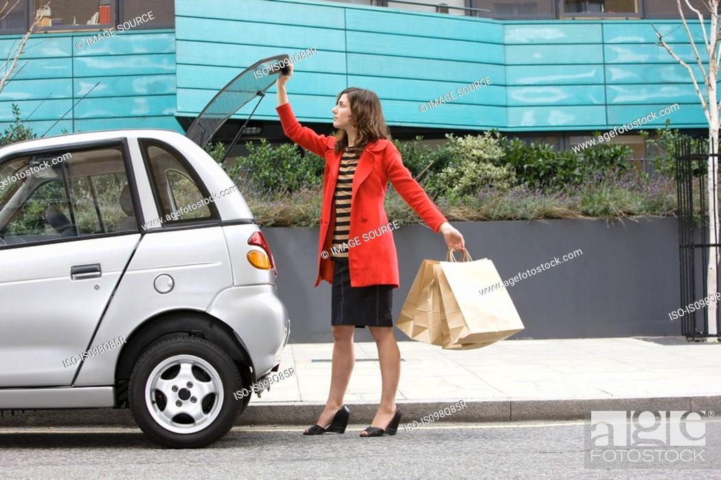Stock Photo: Woman by car with shopping bags.