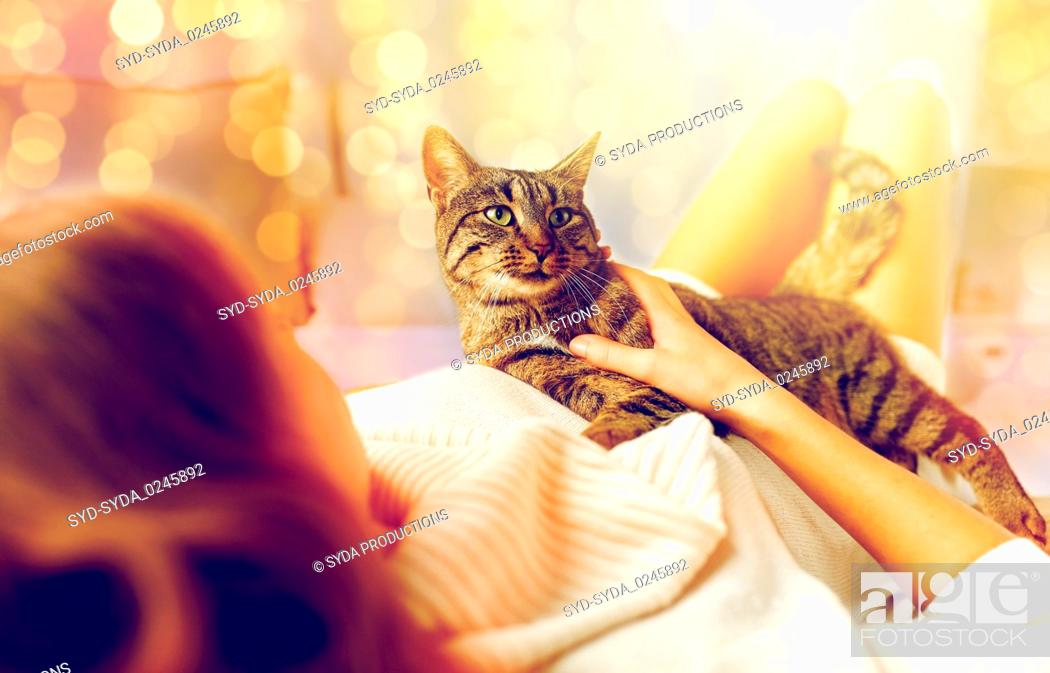 Stock Photo: happy young woman with cat lying in bed at home.