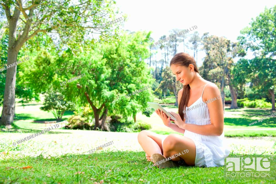 Stock Photo: Side view of woman on the lawn with her tablet computer.