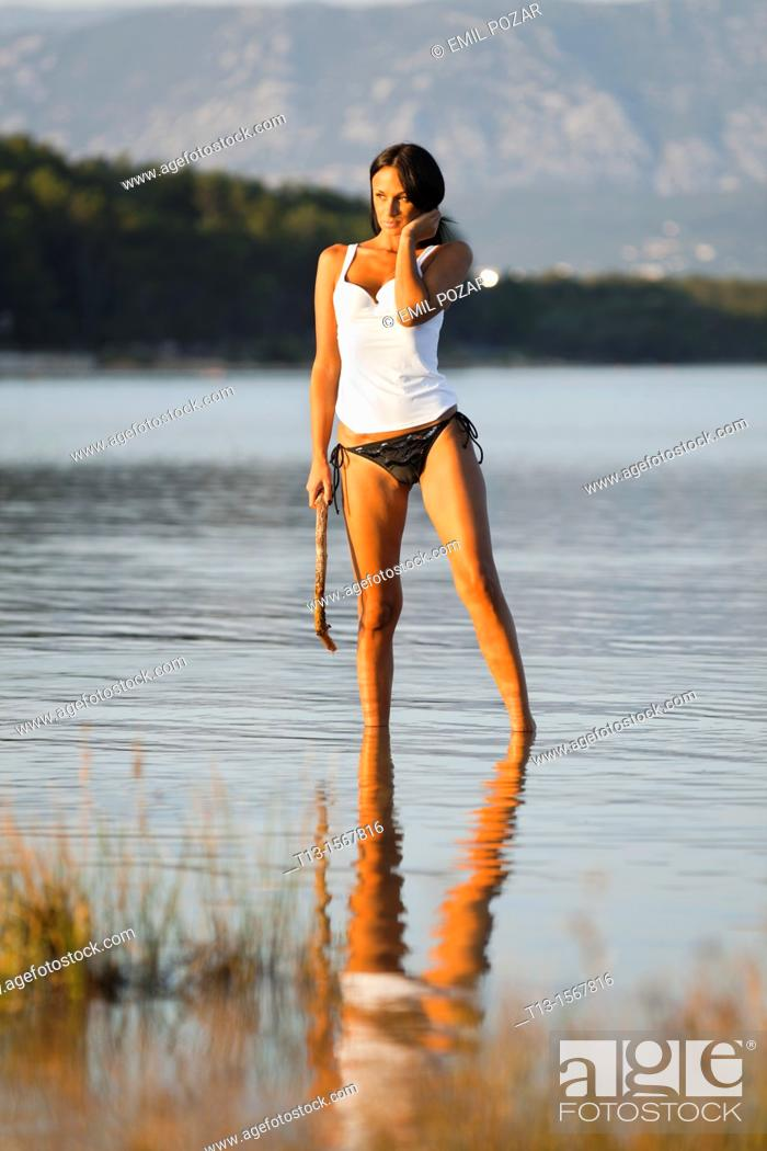 Stock Photo: Young woman is standing in a shallow water with a tree branch in hand.